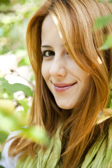 Beautiful young redhead woman standing near the apple tree