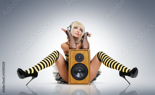 Glamour sexy young girl in headphones with speaker