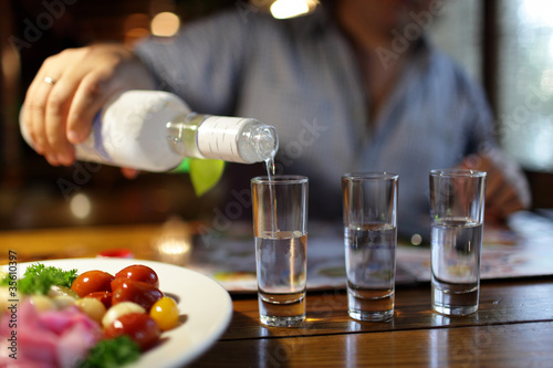 Man pouring vodka in pub