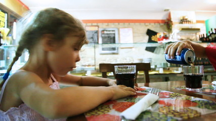 Little girl sits at table and hand boy pours into glasses water