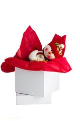 Red and white toy snowman in holiday gift box.