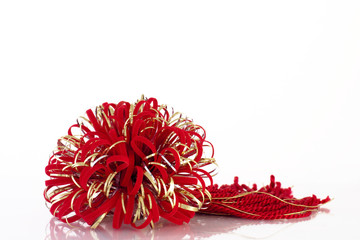 Red and gold decorative bow and tassel for gift.