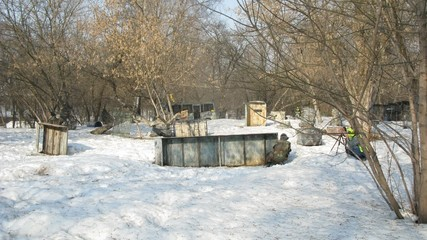 Children and adults play paintball in winter