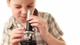 Little boy works with microscope making some research