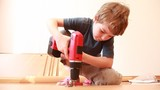Boy use screwdriver while construct furniture element