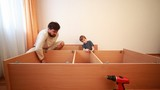 Father tightening screws in board, boy works with hammer