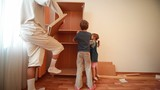 Father and kids construct wooden closet at home