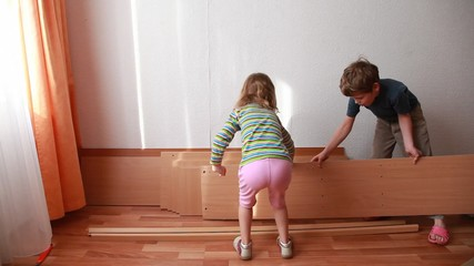 Two little kids place wooden boards