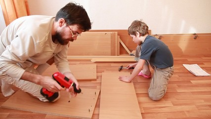 Father and son construct wooden cabinet at home
