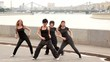 Four girls start dance in modern style synchronously on quay