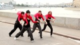 Four girls active dance synchronously on quay