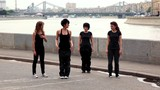 Four girls dance synchronously on quay