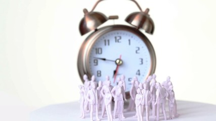 Little uncolored toy men and women stand in front of big clock