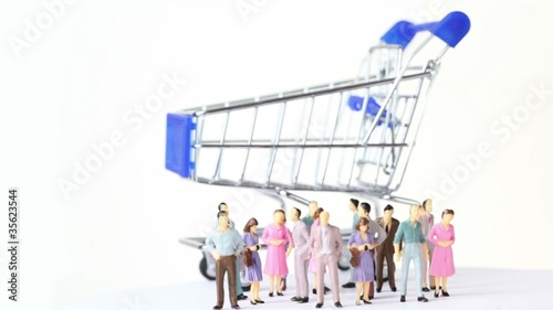 little toy men and women stand in front of shopping trolley