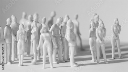 Little uncolored toy men and women stand