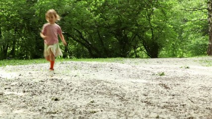 Girl runs closer across forest meadow all strewn fluff