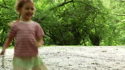 Girl runs closer from far across meadow all strewn fluff