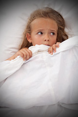 Little girl in bed awaken by nightmares