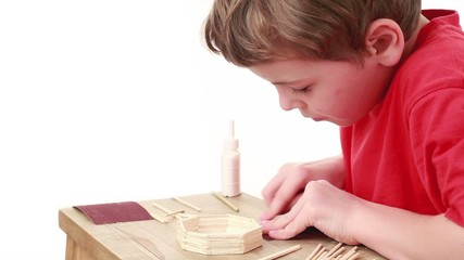 Boy whet match using sandpaper which lies on table for this