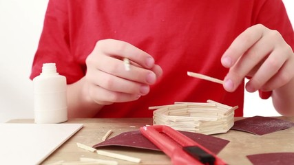 Boy apply glue on stick and attach it to wall of match house