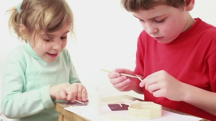 Two kids building match house