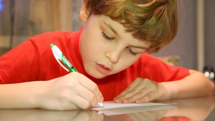 boy writes something very attentively