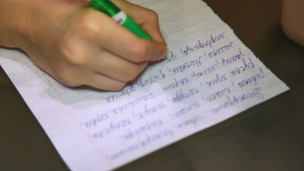 Hand of boy which writes the text on sheet of paper