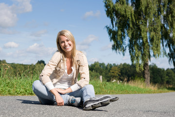 Inline skates young woman sitting asphalt road