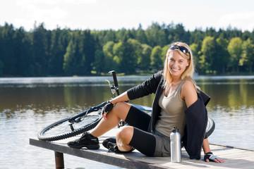 Sport biking young woman sitting by lake