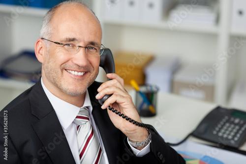 freundlicher geschäftsmann am telefon - 35628573