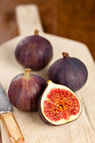 Whole and halved figs on a wooden board