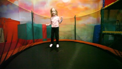 little girl jumps on trampoline in playroom.