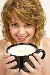 Frau drinkt Kaffee mit viel geschäumter Milch.