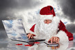 Santa Claus placing orders on his laptop and tablet-pc