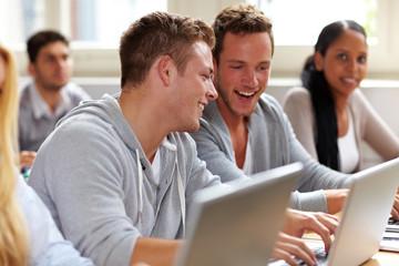 Lachende Männer beim Studium