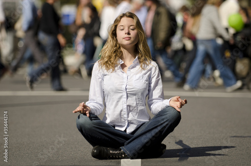 woman meditating in busy urban street
