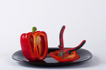 A red pepper and a clamp on a black plate #3