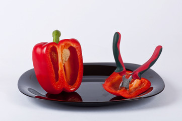A red pepper and a clamp on a black plate #2