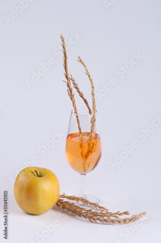 An apple, a glass filled with orange substance and spice