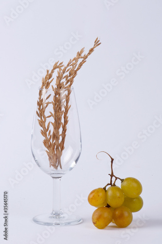 A glass filled with spice and a bunch of grapes #2