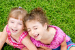 children girls laughing sit on green grass