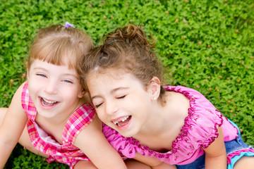 children girls laughing sit on green grass