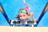 blond little girl in swimming pool with goggles