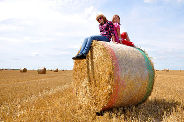 children sitting on a bale of straw