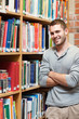 Portrait of a smiling male student leaning on a shelf