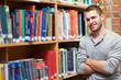 Smiling male student leaning on a shelf