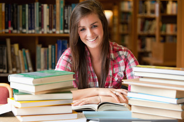 Smiling student having a lot to read