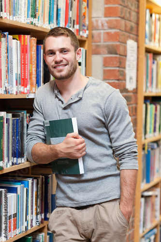 Portrait of a smiling male student holding a book