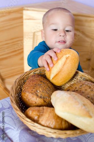 Leinwandbild Motiv Kleiner Junge nascht vom Brotkorb