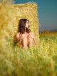 beautiful nude woman sitting near hay stack